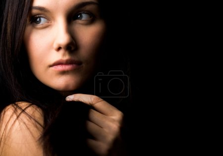 Photo for Image of gorgeous lady with dark hair touching it by hand and looking aside - Royalty Free Image