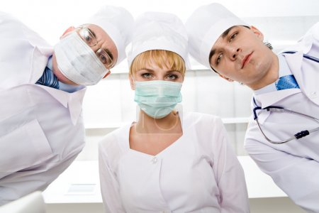 Photo for Below view of three therapeutists in masks looking at camera - Royalty Free Image