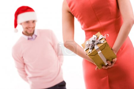 Photo for Rear view of woman in red dress holding giftbox in hand on background of her husband - Royalty Free Image