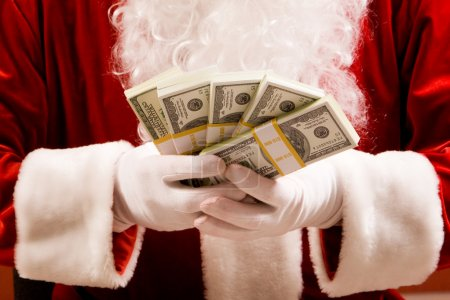 Santa hands with stacks of dollar banknotes