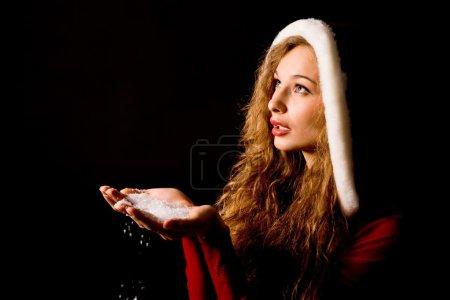 Photo pour Portrait de jolie fille avec de la neige sur ses paumes sur fond sombre - image libre de droit