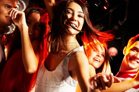 Photo pour Image de fille énergique regardant la caméra tout en dansant sur le fond de ses amis - image libre de droit