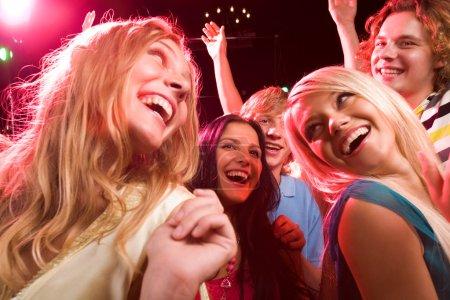 Photo pour Plusieurs danseurs souriants s'amuser au cours de disco - image libre de droit