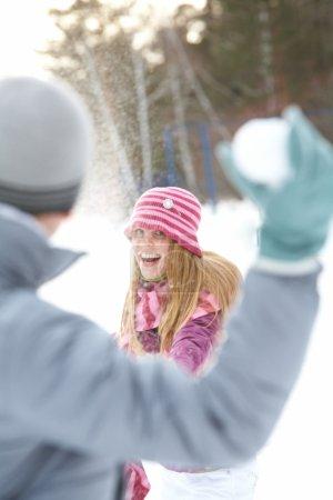 Photo pour Image de jolie jeune femme jetant la boule de neige et de s'amuser - image libre de droit