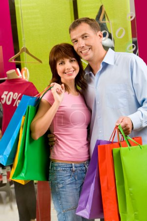 Photo for Portrait of shopaholics holding paperbags and smiling at camera - Royalty Free Image