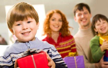 Photo pour Portrait de garçon heureux avec présent regardant la caméra sur fond de ses parents et son frère - image libre de droit
