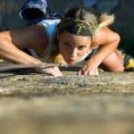 Attractive girl climbs a granite rock...