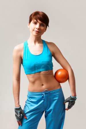 Photo for Portrait of sporty woman with ball between arm and waist looking at camera - Royalty Free Image
