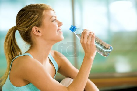 Photo for Profile of beautiful woman going to drink some water fron plastic bottle after workout - Royalty Free Image