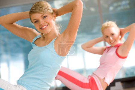 Photo for Photo of cheerful girl doing exercise in sport gym with another woman at background - Royalty Free Image