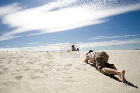 Photo pour Photographe prudent prendre des photos de couple relaxant assis dos à dos sur la plage de sable contre le ciel bleu - image libre de droit