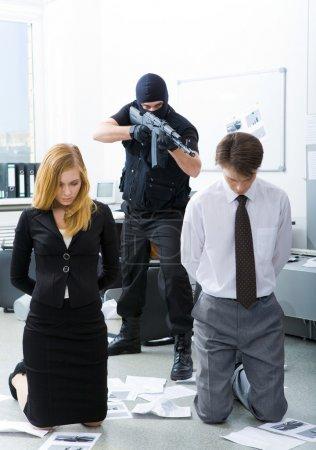 Photo pour Photo de leurs collègues d'affaires debout sur les genoux déployés visent par mal terroriste - image libre de droit
