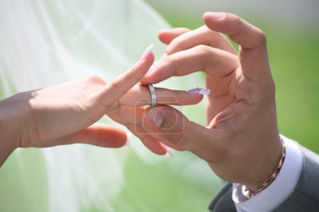 Close-up of grooms hand putting wedding ring on br...