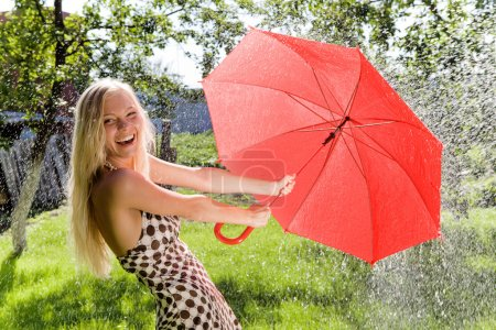 Photo for Portrait of happy girl with red umbrella in hands laughing at camera in park - Royalty Free Image