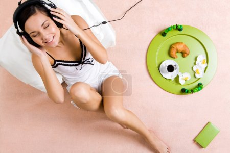 Photo for Above view of happy girl sitting on bed and listening to music in headphones - Royalty Free Image