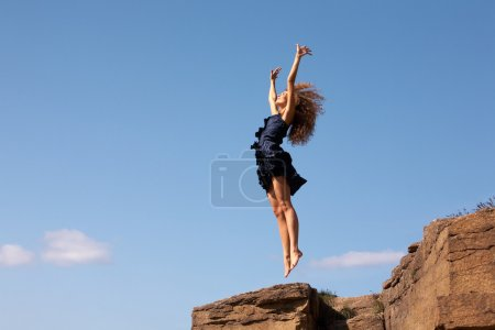 Photo for Photo of delighted female leaping over rocky cliff in excitement - Royalty Free Image