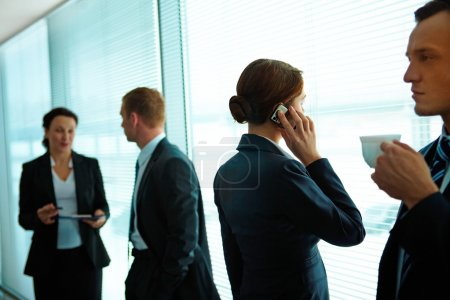 Photo for Four business partners interacting in office - Royalty Free Image