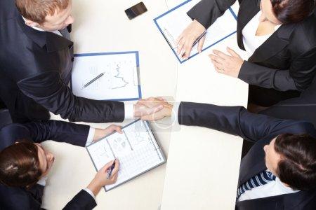 Photo pour Ci-dessus vue de handshaking partenaires commerciaux après la signature du contrat - image libre de droit
