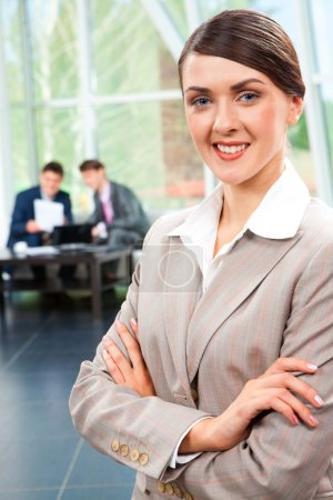 Photo for Portrait of smiling businesswoman folding her hands and looking at camera in the room - Royalty Free Image