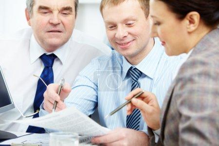Photo pour Image de collègues confiants, discutant des papiers à la réunion - image libre de droit