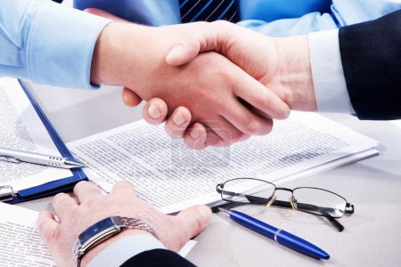 Photo for Close-up of business handshake over workplace with documents, pens, glasses - Royalty Free Image