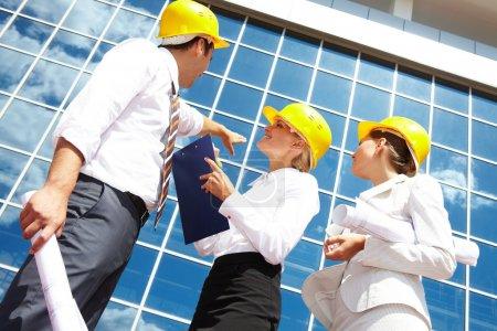 Photo pour Ci-dessous vue des partenaires commerciaux dans les casques regardant immeuble de bureaux moderne - image libre de droit