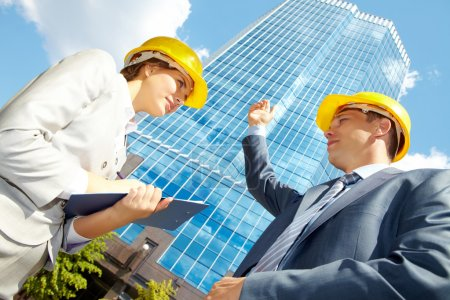 Photo for Below view of confident architect pointing at modern office building and looking at pretty co-worker in helmet - Royalty Free Image