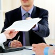 Close-up of handing over documents during business...