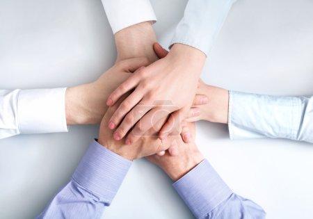 Photo pour Vue ci-dessus de partenaires d'affaires mains sur l'autre symbolisant la compagnie et l'unité - image libre de droit