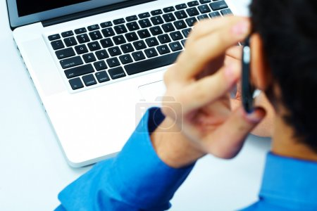 Photo of open laptop with calling businessman near by