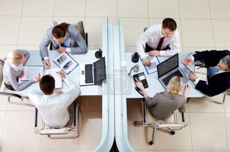 Photo pour Vue de dessus de deux équipes d'affaires travaillant et interagissant séparées par des frontières au bureau - image libre de droit