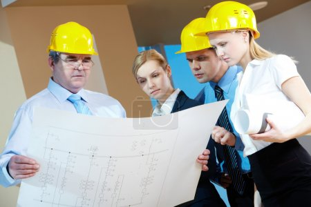 Photo for Portrait of mature worker holding a project with three colleagues near by - Royalty Free Image
