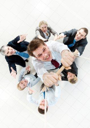 Photo pour Vue ci-dessus de l'homme d'affaires tenant la planche sur des cordes et accrochant dessus avec l'équipage de soutien en dessous - image libre de droit