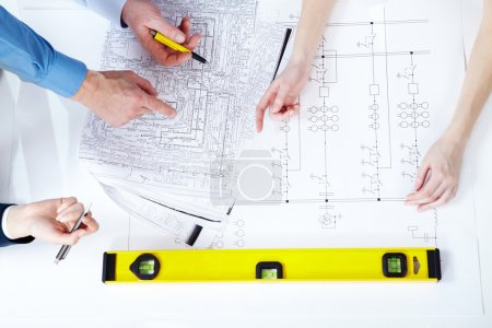 Photo for Above view of worker's hands pointing to design project - Royalty Free Image