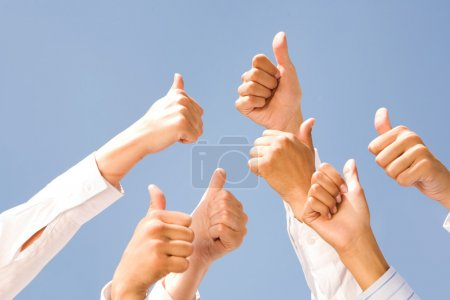 Photo for Image of several human hands showing thumbs up against clear blue sky - Royalty Free Image