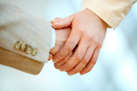 Photo for Human hands holding those of business partner symbolizing help and support - Royalty Free Image