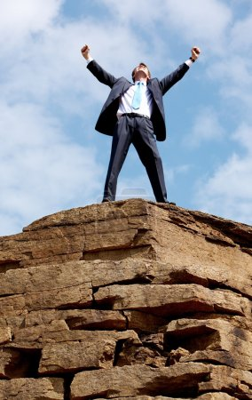 Photo for Happy businessman standing on the top of mount with his arms raised to the sky - Royalty Free Image