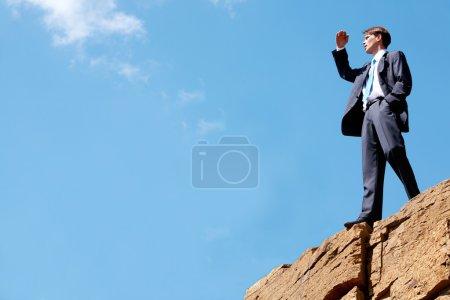 Photo pour Photo d'homme d'affaires heureux debout sur la falaise et en regardant au loin sur fond de ciel lumineux - image libre de droit