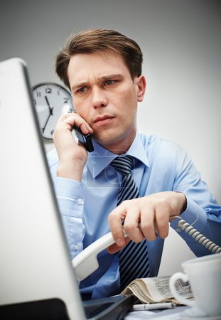 Photo for Portrait of serious businessman looking at laptop screen while calling by cellphone - Royalty Free Image