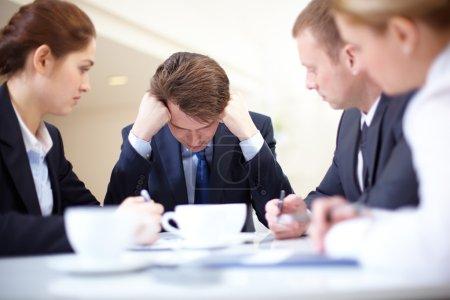 Photo pour Image d'homme d'affaires frustré toucher sa tête tandis que ses collègues lui en regardant à la réunion - image libre de droit