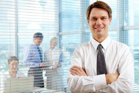 Photo pour Femme à la tête regardant la caméra avec deux partenaires interagissant au bureau derrière - image libre de droit