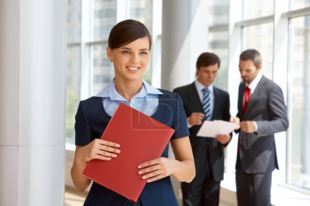 Photo for Portrait of confident female looking aside with working colleagues at background - Royalty Free Image