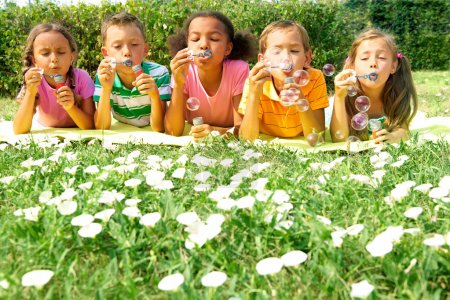 Photo for Portrait of cute friends having bubble fun on green lawn in park - Royalty Free Image