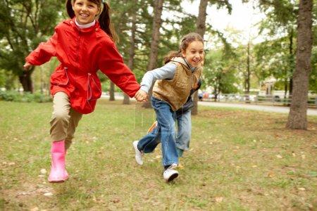 Photo pour Portrait d'enfants heureux courant ensemble dans le parc automnal - image libre de droit