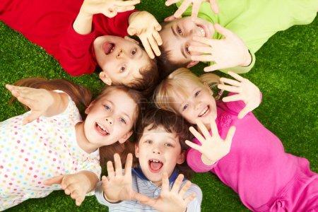 Photo pour Image de jeunes garçons et filles souriants allongés sur de l'herbe verte et montrant des paumes - image libre de droit