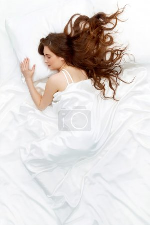 Photo for Above view of young beautiful woman sleeping in bed covered with white silky sheet - Royalty Free Image
