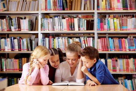 Photo pour Portrait des élèves et des enseignants à la recherche à la page d'un livre intéressant dans la bibliothèque - image libre de droit