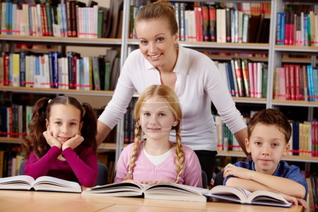 Photo for Portrait of pupils and teacher looking at camera with smiles in library - Royalty Free Image