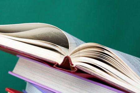 Photo pour Pile colorée de manuels avec livre ouvert sur son dessus - image libre de droit