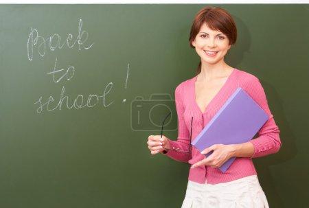 Photo pour Portrait de jeune professeur avec livre et lunettes regardant la caméra au tableau noir - image libre de droit